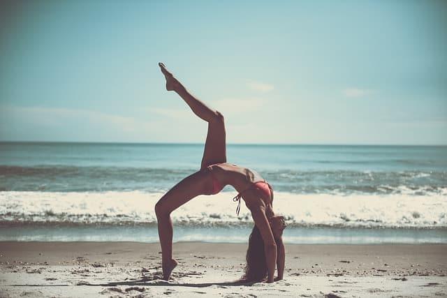 Junge, trainierte Frau macht Yoga am Strand