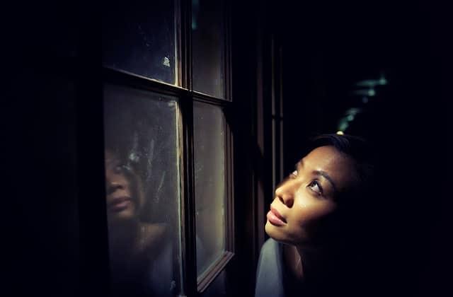 Junge Frau im Dunkeln am Fenster