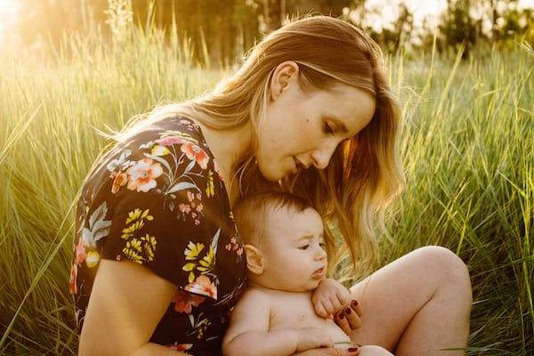 EIne Frau sitzt mit einem Baby am Schoß in hohem Gras