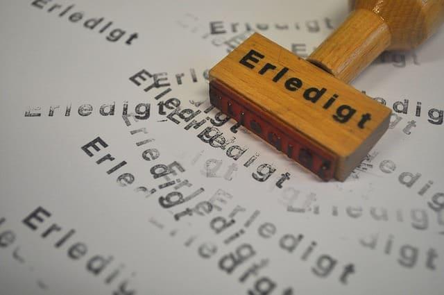 Stempel mit der Aufschrift ' Erledigt' auf einem zugestempelten Papier