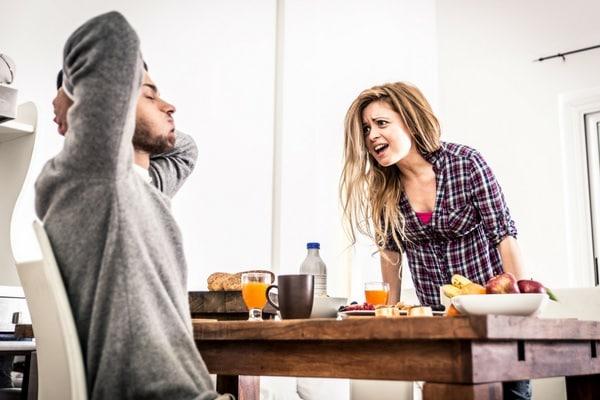 Seitensprung - und nun? Streitendes Paar am Frühstückstisch. Frau schreit Mann an, der sprachlos beide Arme verschränkt.