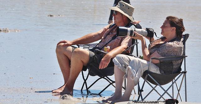 Älteres, zufriedenes Paar sitzt auf Strandstühlen im Sand und Frau hat eine Kamera in der Hand