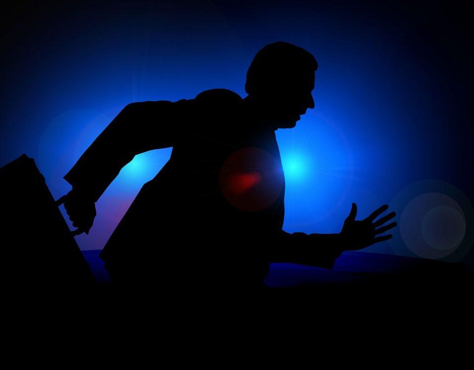 Ein Mann läuft mit einer Aktentasche vor dunklem Hintergrund