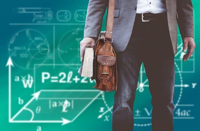Eine grüne Schultafel mit vielen Formeln und Diagrammen, davor steht ein Mann mit Unitasche und Buch