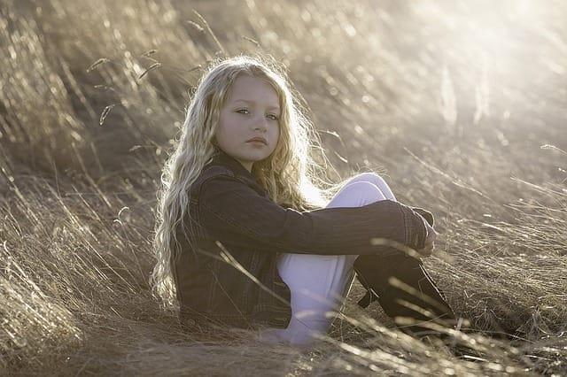 Blondes Mädchen sitzt im Streu und hat einen nachdenklichen Blick