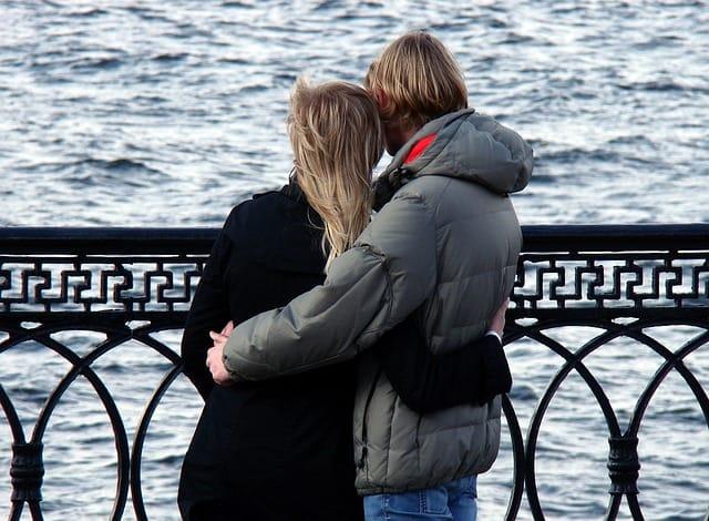 Glückliches Paar steht umarmend auf einer Brücke und schaut in denn Fluss